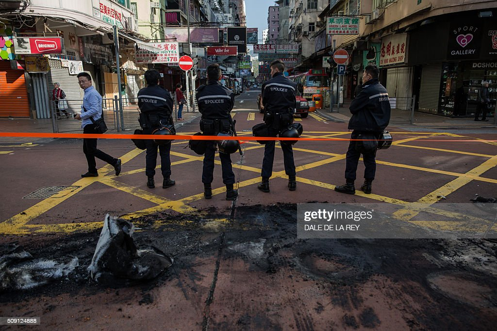 Hong Kong policemen cordon off an area next to burnt debris following overnight clashes between protesters and police in the Mongkok area of Hong Kong on February 9, 2016. Baton-wielding Hong Kong riot police fired warning shots and tear gas early on February 9 after a riot erupted in the busy district of Mongkok when officials tried to shift illegal hawkers, local radio reported. AFP PHOTO / DALE DE LA REY / AFP / DALE de la REY