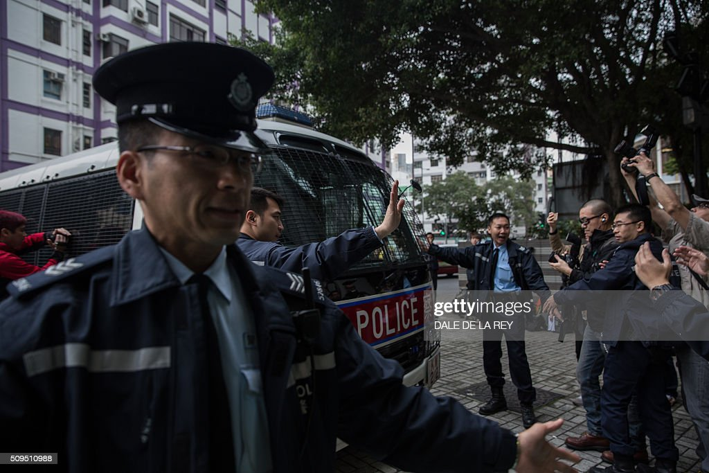 Hong Kong policemen escort a vehicle carrying protesters, who are facing one count each of taking part in a riot on February 9 in the Mongkok district, to a court building in Hong Kong on February 11, 2016. More than 30 people were expected to appear in court charged with rioting after clashes erupted in the city over official attempts to remove illegal street hawkers during the Lunar New Year. AFP PHOTO / DALE DE LA REY / AFP / DALE de la REY