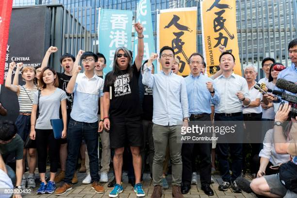 Hong Kong prodemocracy activists and lawmakers hold a protest against their recent arrests and detention ahead of the visit by China's President Xi...