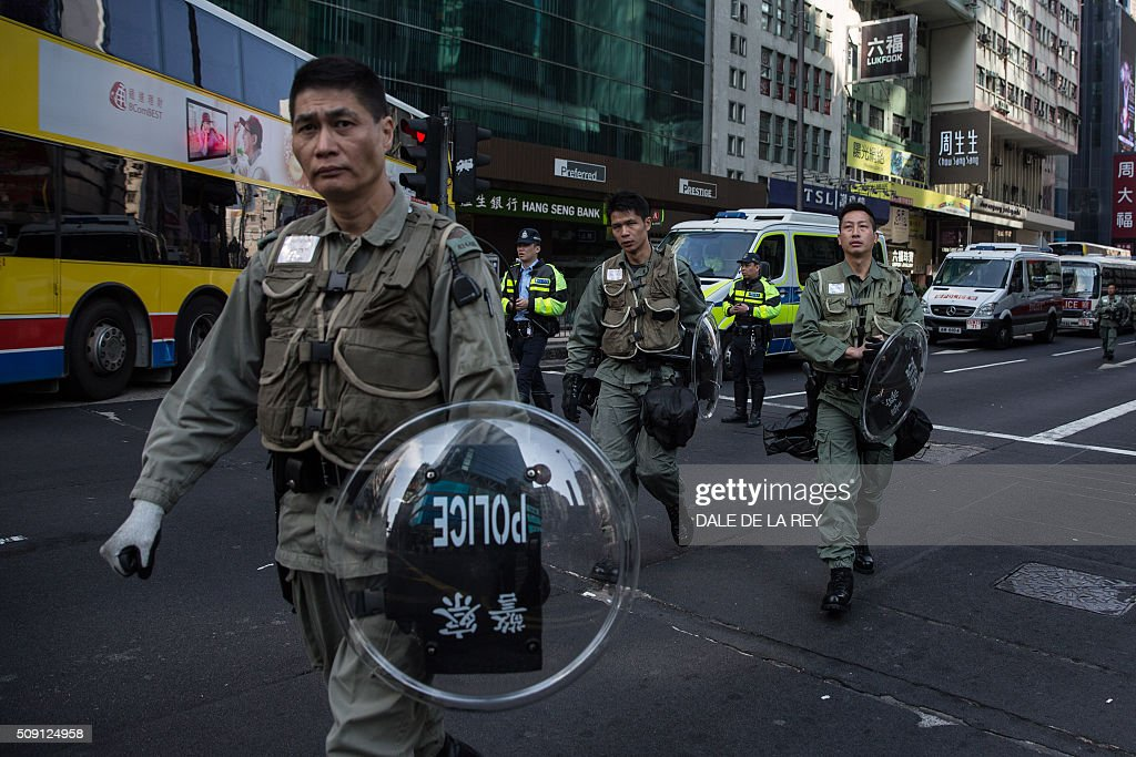 Hong Kong riot police walk along a cordoned-off street following overnight clashes between protesters and police in the Mongkok area of Hong Kong on February 9, 2016. Baton-wielding Hong Kong riot police fired warning shots and tear gas early on February 9 after a riot erupted in the busy district of Mongkok when officials tried to shift illegal hawkers, local radio reported. AFP PHOTO / DALE DE LA REY / AFP / DALE de la REY