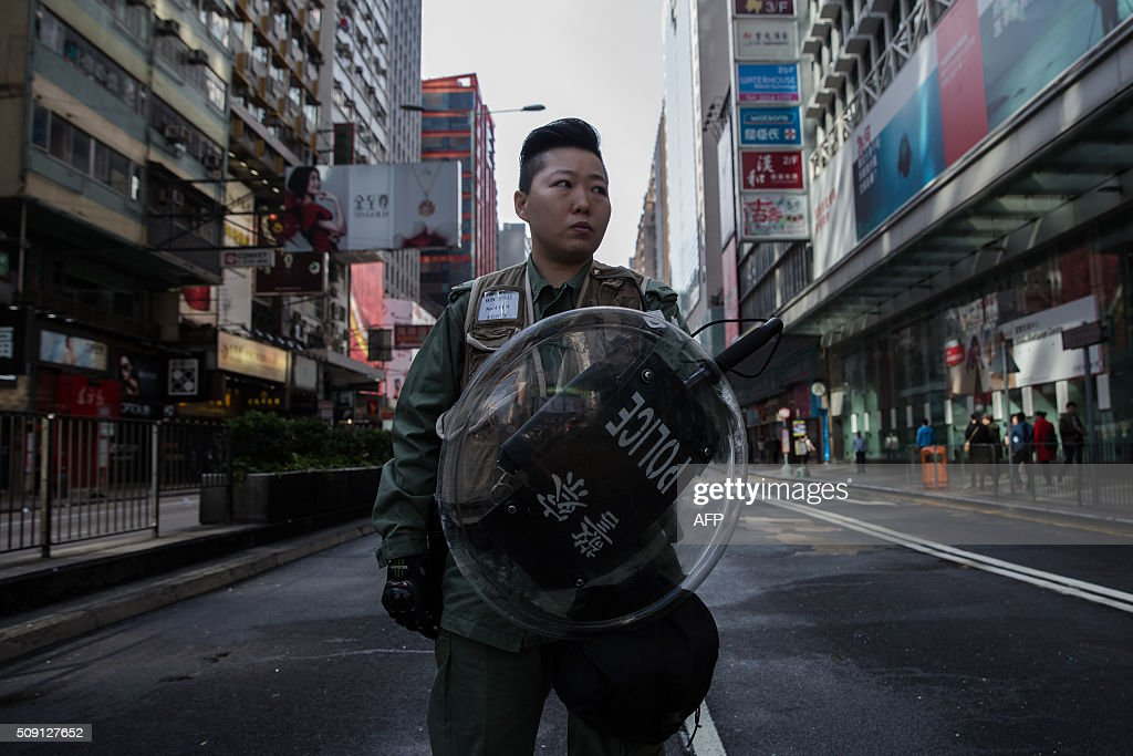 A Hong Kong riot policewoman stands on a cordoned-off street following overnight clashes between protesters and police in the Mongkok area of Hong Kong on February 9, 2016. Baton-wielding Hong Kong riot police fired warning shots and tear gas early on February 9 after a riot erupted in the busy district of Mongkok when officials tried to shift illegal hawkers, local radio reported. AFP PHOTO / DALE DE LA REY / AFP / DALE de la REY