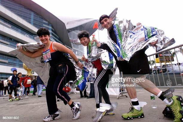Hong Kongbased runners with a taste for hamming it up show their style at the finish line of the 2001 Standard Chartered Hong Kong Marathon 04...
