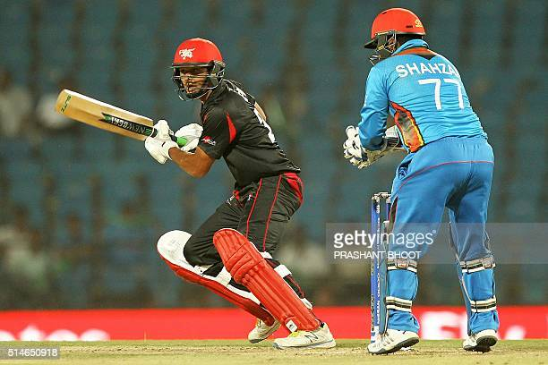 Hong Kong's Anshuman Rathplays a shot past Afghanistan's wicketkeeper Mohammad Shahzad during the World T20 cricket tournament match between...