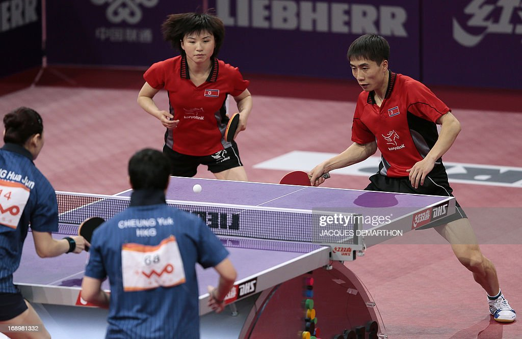 Hong Kong's Cheung Yuk (bottom, R) and Jiang Huajun (bottom, L) compete against to North Korea's Kim Hyok Bong (R, back) and Kim Jong on May 18, 2013 in Paris , during their mixed double semi-final at the World Table Tennis Championships. AFP PHOTO/JACQUES DEMARTHON
