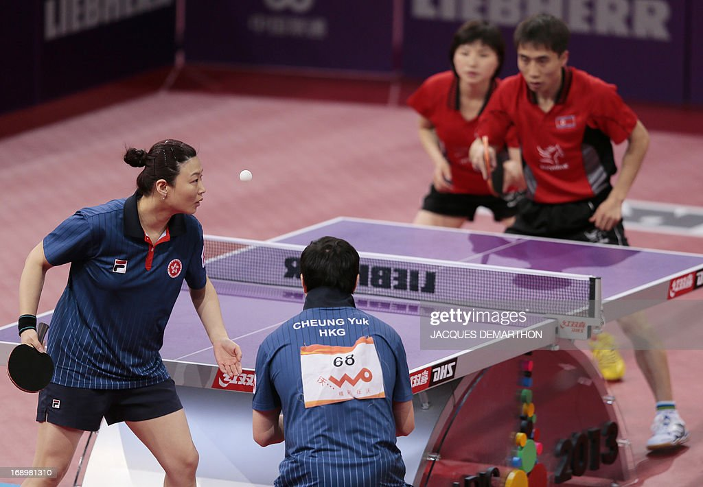 Hong Kong's Cheung Yuk (bottom, R) and Jiang Huajun (bottom, L) serve to North Korea's Kim Hyok Bong (R, back) and Kim Jong on May 18, 2013 in Paris , during their mixed double semi-final at the World Table Tennis Championships. AFP PHOTO/JACQUES DEMARTHON