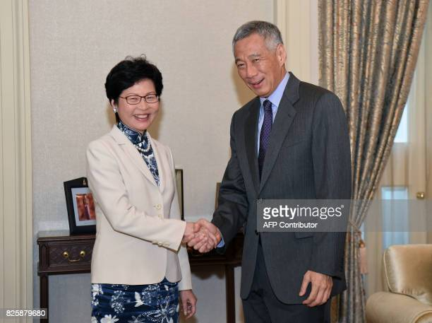 Hong Kong's Chief Executive Carrie Lam shakes hands with Singapore Prime Minister Lee Hsien Loong during a call at Istana presidential palace in...