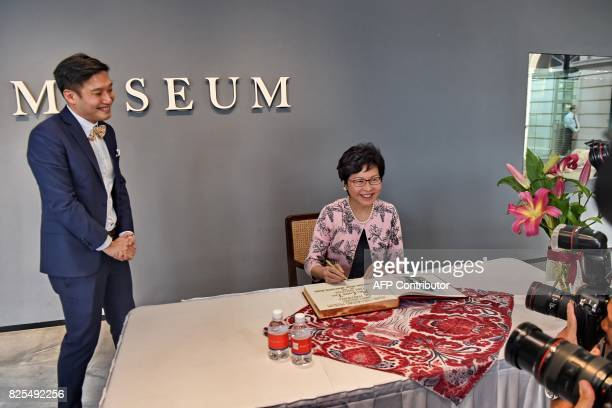 Hong Kong's Chief Executive Carrie Lam signs a guest book during her tour of the Tang Shipwreck Gallery at the Asian Civilisation Museum in Singapore...