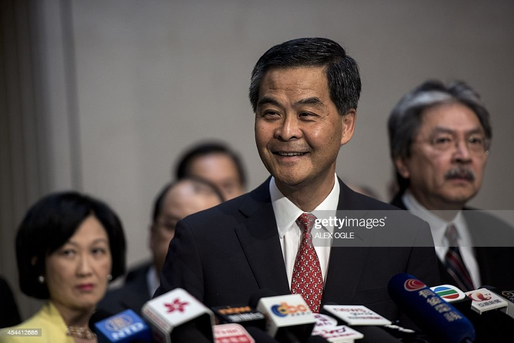 Hong Kong's Chief Executive Leung Chun-ying (C) smiles before answering a question at a press conference on political reform at the government headquarters in Hong Kong on August 31, 2014. China insisted on August 31 that candidates for Hong Kong's next leader must be screened in advance, triggering tears and fury in the former British colony where democracy advocates said they would occupy the financial district. AFP PHOTO / ALEX OGLE