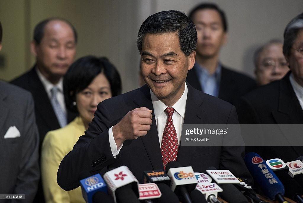Hong Kong's Chief Executive <a gi-track='captionPersonalityLinkClicked' href=/galleries/search?phrase=Leung+Chun-ying&family=editorial&specificpeople=2496883 ng-click='$event.stopPropagation()'>Leung Chun-ying</a> (C) smiles before answering a question at a press conference on political reform at the government headquarters in Hong Kong on August 31, 2014. China insisted on August 31 that candidates for Hong Kong's next leader must be screened in advance, triggering tears and fury in the former British colony where democracy advocates said they would occupy the financial district. AFP PHOTO / ALEX OGLE