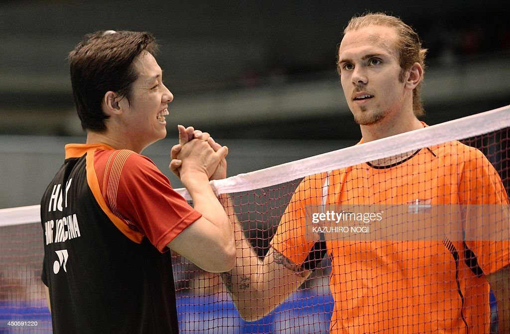 Hong Kong's Hu Yun (L) shakes hands with Denmark's Jan O Jorgensen after winning their men's singles semi-final match at the Japan Open badminton tournament in Tokyo on June 14, 2014.