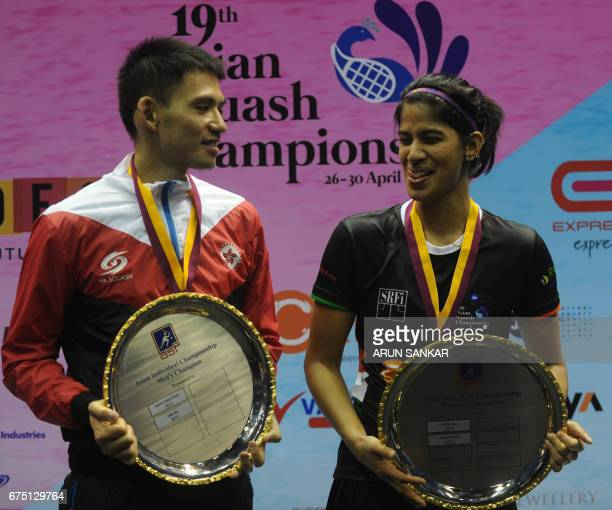 Hong Kong's Max Lee and India's Joshana Chinnappa pose with their winners' trophies after the final matches at the 19th Asian Squash Championship in...