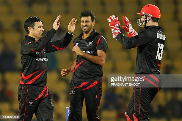 Hong Kong's Ryan Campbell Tanwir Afzal and Jamie Atkinson celebrate the dismissal of Afghanistan's batsman Mohammad Shahzad during the World T20...