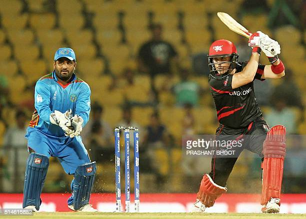 Hong Kong's Ryan Campbellis watched by Afghanistan's wicketkeeper Mohammad Shahzad as he plays a shot during the World T20 cricket tournament match...