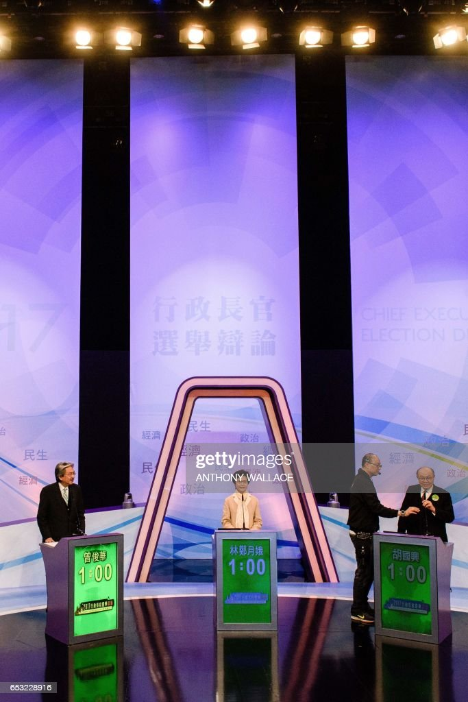 Hong Kong's three leadership candidates John Tsang (L), Carrie Lam (C) and ex-judge Woo Kwok-hing (R) stand on stage at a studio before facing off in their first televised debate in Hong Kong on March 14, 2017. Hong Kong's three leadership candidates faced off in their first televised debate on March 14 as criticism mounts over a voting process which favours Beijing and bypasses the majority of the electorate. / AFP PHOTO / Anthony WALLACE