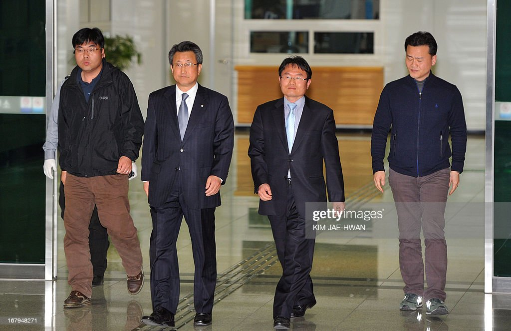 Hong Yang-Ho (2nd L), head of the Kaesong Industrial District Management Committee, arrives at a border checkpoint in Paju on May 3, 2013, as he returns from the closed joint industrial zone after talks with North Korean officials. South Korea on May 3 withdrew its last remaining workers from the zone at risk of permanent closure due to soaring military tensions.