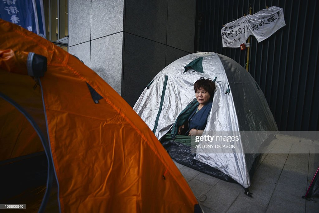 HongKong-China-politics,ANALYSIS by Beh Lih Yi A demonstrator looks out from a tent as she camps out at the government headquarters during a protest against the city's leader Leung Chun-ying in Hong Kong on January 2, 2013. Hong Kong's beleaguered leader faces a huge task to bridge a widening political gap, analysts said, after a mass rally pushing for his resignation and a swifter path to democracy under Chinese rule. Tens of thousands of people marched on New Year's Day in two opposing demonstrations, heaping pressure on the city's Beijing-backed chief executive Leung Chun-ying who is also embroiled in an embarrassing renovations scandal. AFP PHOTO / Antony DICKSON