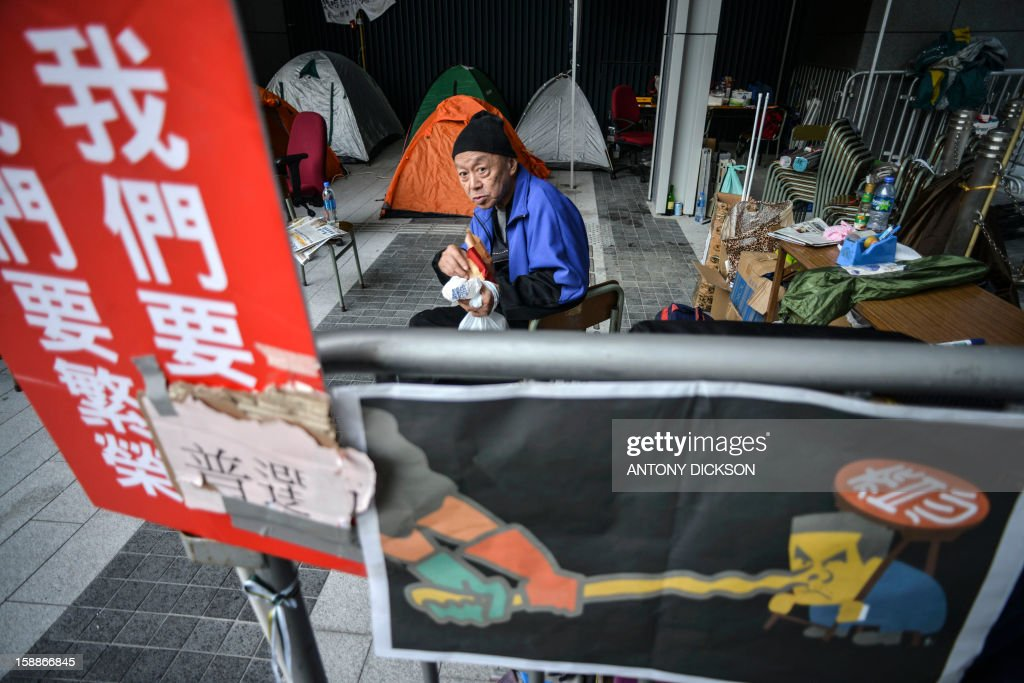 HongKong-China-politics,ANALYSIS by Beh Lih Yi A demonstrator sits in front of tents as people camp out at the government headquarters during a protest against the city's leader Leung Chun-ying in Hong Kong on January 2, 2013. Hong Kong's beleaguered leader faces a huge task to bridge a widening political gap, analysts said, after a mass rally pushing for his resignation and a swifter path to democracy under Chinese rule. Tens of thousands of people marched on New Year's Day in two opposing demonstrations, heaping pressure on the city's Beijing-backed chief executive Leung Chun-ying who is also embroiled in an embarrassing renovations scandal. AFP PHOTO / Antony DICKSON