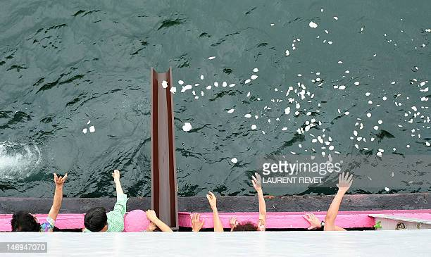 HongKongsocietyfuneralcemeteryFEATURE by Beh Lih Yi This photo taken on May 5 2012 shows family members throwing flower petals into the sea during a...
