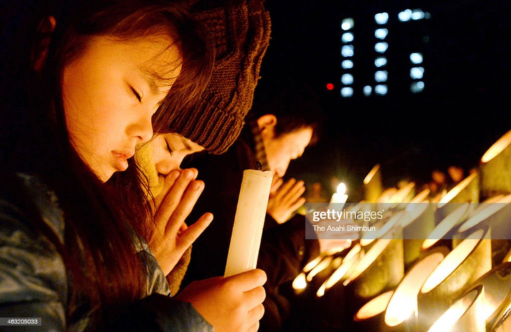 Honoka Nakakuma, 7, left, with her mother, Nahoko, 28, pray at 5:46 am in memory of Honoka's uncle, who died when his home collapsed in the Great Hanshin Earthquake in 1995 at Higashi Yuenchi park on January 17, 2014 in Kobe, Hyogo, Japan. Mourners packed the park to remember the exact moment when the Great Hanshin Earthquake struck 19 years ago, devastating the city and killing 6,434 people.