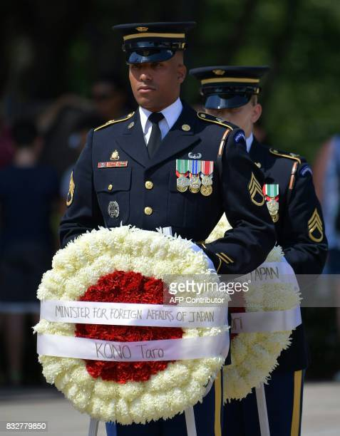 US honor guard offcier holds a wreath before Japan's Foreign Minister Tar Kno and Defense Minister Itsunori Onodera to lay it at the Tomb of the...