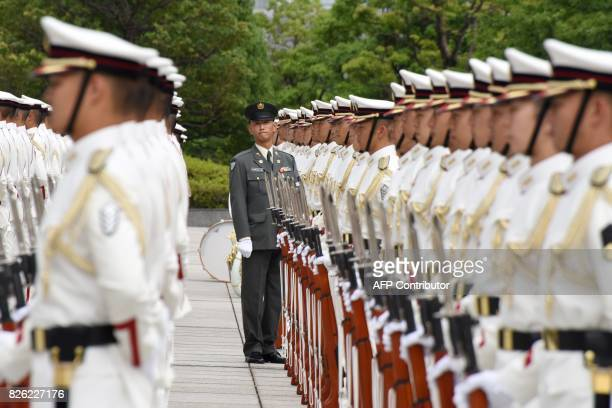 TOPSHOT Honor guards make a line prior to a welcoming ceremony for Japan's new Defence Minister Itsunori Onodera at the Defence Ministry in Tokyo on...