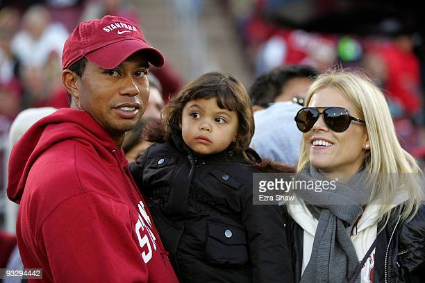 Honorary Standford Cardinal captain Tiger Woods holds his daugher Sam and stands next to his wife Elin Nordegren on the sidelines before the Cardinal...