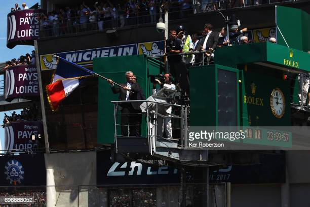 Honorary starter Chase Carey CEO and Executive Chairman of the Formula One Group waves the French flag to start the Le Mans 24 Hours race at the...