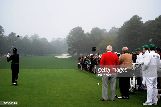 Honorary starter Gary Player of South Africa tees off as Arnold Palmer of the United States and Jack Nicklaus of the United States look on to start...