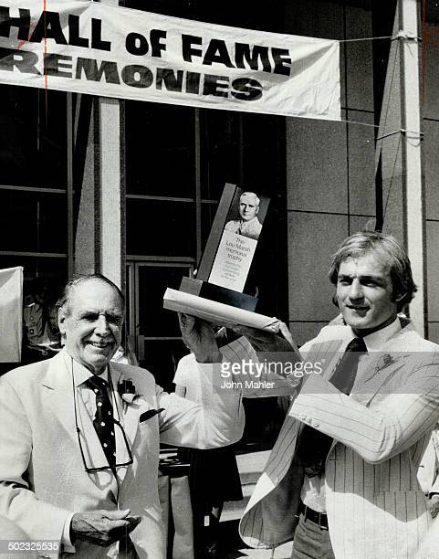 Honored Montreal Canadiens' star Guy Lafleur accepts the Lou Marsh Trophy as Canada's outstanding athlete of 1977 from committee chairman Harry Red...