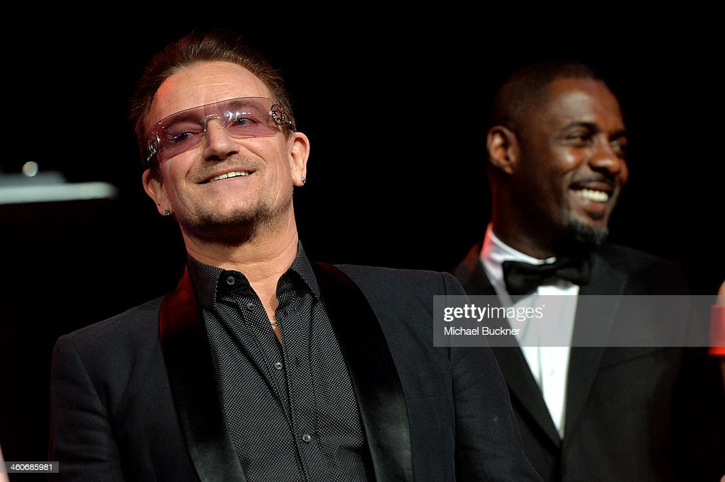 Honoree Bono accepts the Sonny Bono Visionary award from actor Idris Elba onstage during the 25th annual Palm Springs International Film Festival awards gala at Palm Springs Convention Center on January 4, 2014 in Palm Springs, California.
