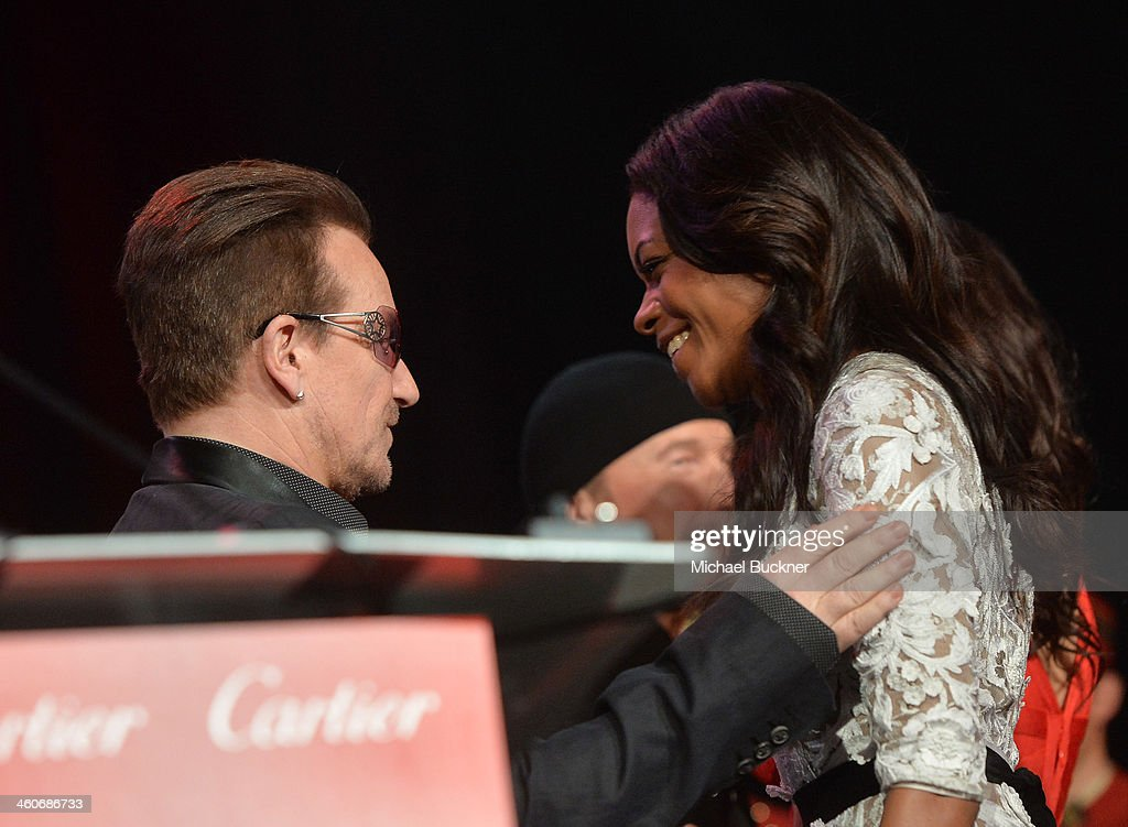 Honoree Bono accepts the Sonny Bono Visionary award from actress Naomie Harris onstage during the 25th annual Palm Springs International Film Festival awards gala at Palm Springs Convention Center on January 4, 2014 in Palm Springs, California.