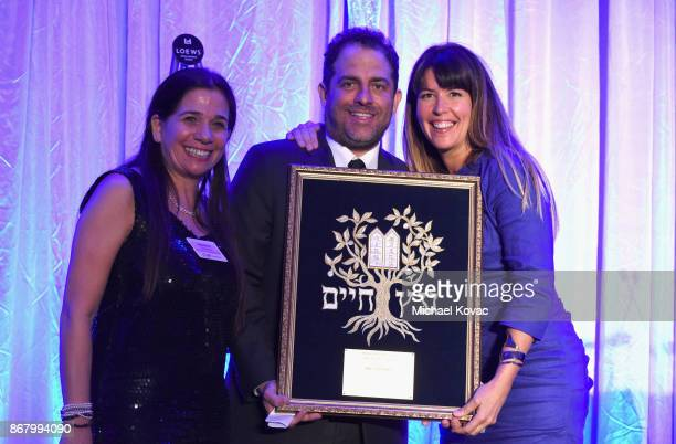 Honoree Brett Ratner accepts the Tree of Life Award from Patty Jenkins and Sharon Freedman onstage during the Jewish National Fund Los Angeles Tree...