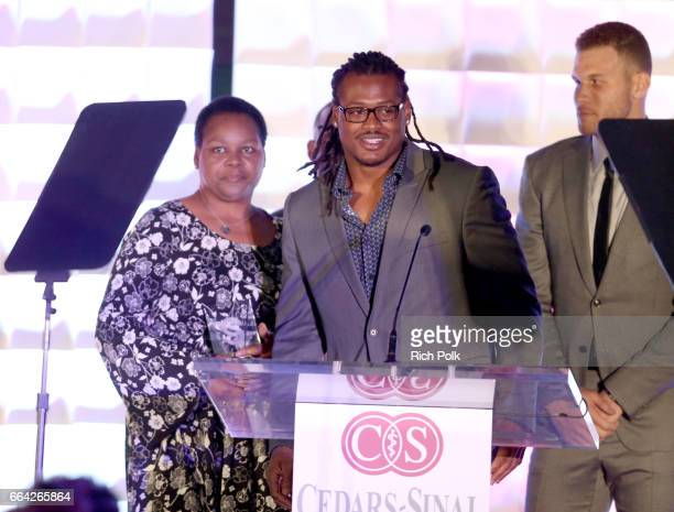 Honoree Dont'a Hightower accepts the Spirit Award from NBA players Chris Paul and Blake Griffin onstage during 32nd Annual CedarsSinai Sports...