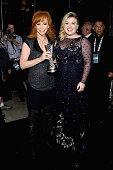 Honoree Reba McEntire holding the 50th Anniversary Milestone Award and recording artist Kelly Clarkson pose backstage at the 50th Academy Of Country...