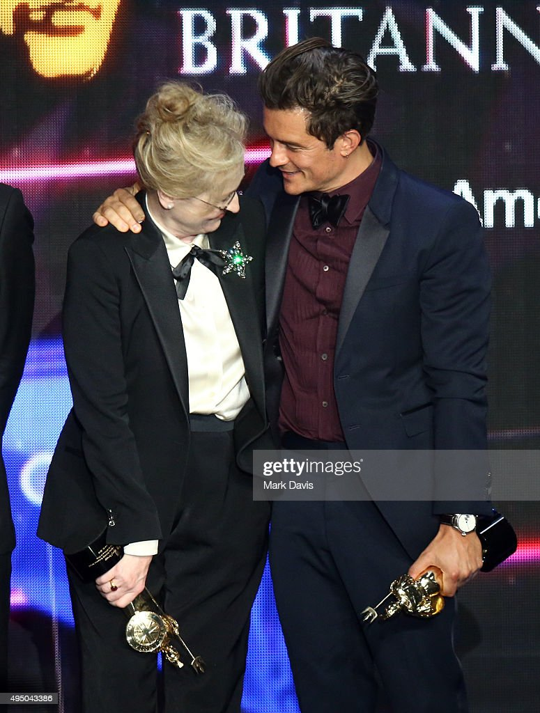 Honorees Meryl Streep (L) (holding the Stanley Kubrick Britannia Award for Excellence in Film) and Orlando Bloom (holding the Britannia Humanitarian Award presented by The Beazley Group) stand onstage during the 2015 Jaguar Land Rover British Academy Britannia Awards presented by American Airlines at The Beverly Hilton Hotel on October 30, 2015 in Beverly Hills, California.