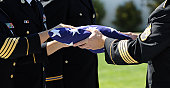 Officers Of A Military Honor Guard carefully prepare a flag that graced the casket of one of America's fallen heros.