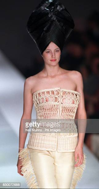 Honour Frazer models an ivory cane bodice with matching fringed trousers and black headdress from Antonio Berardi on show for the first day of London...