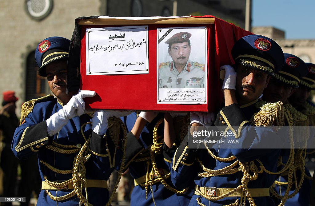 Honour guard soldiers carry the coffin of General Nasser Naji bin Farid, commander of military forces in central Yemen, during the funeral procession for military officers in Sanaa on December 10, 2012, who killed in an ambush earlier in the week. Four officers were killed and six soldiers wounded in the attack by armed men on December 8, near Marib, 140 kilometres east of Sanaa, blamed on Al-Qaeda. AFP PHOTO/ MOHAMMED HUWAIS