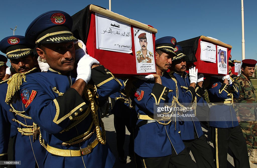 Honour guard soldiers carry the coffins of military officers during their funeral procession in Sanaa on December 10, 2012, who were killed in an ambush on December 8. Four officers were killed, including General Nasser Naji bin Farid, commander of military forces in central Yemen, and six soldiers wounded in the attack by armed men, near Marib, 140 kilometres east of Sanaa, blamed on Al-Qaeda. AFP PHOTO/ MOHAMMED HUWAIS