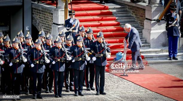 Honour guards stand at attention as a man vacuums the red carpet on Prinsjesdag in The Hague on September 20 2016 Prince's Day is the openingday of...