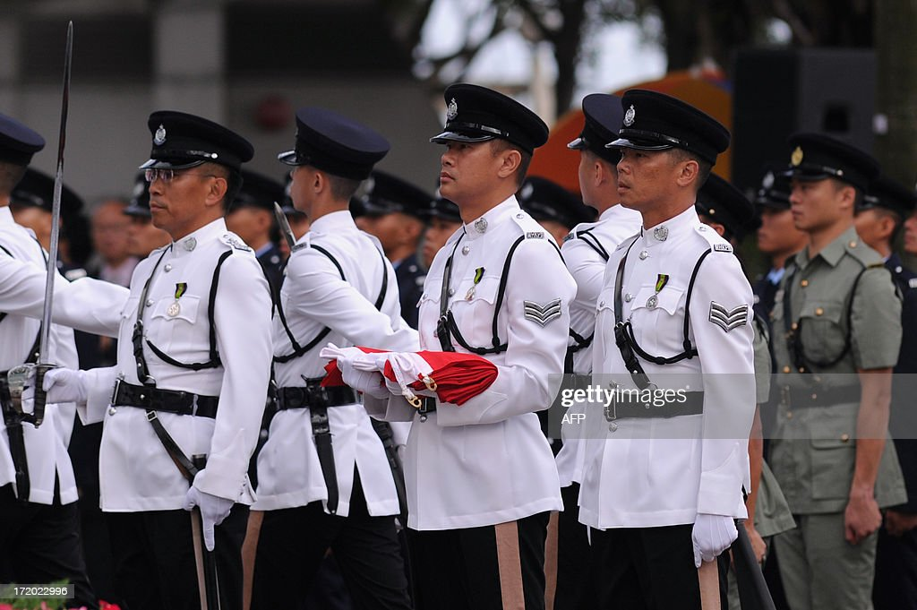 Honour guards (front) stand to attention before the Hong Kong and Chinese flags are hoisted during a flag-raising ceremony at Golden Bauhinia Square in Hong Kong on July 1, 2013 to celebrate the 16th anniversary of the establishment of the Hong Kong Special Administrative Region (HKSAR). Hundreds of thousands of protesters, some waving British colonial-era flags and some sporting Edward Snowden masks, are to march in Hong Kong to denounce the city's leaders and demand universal suffrage on the handover anniversary.