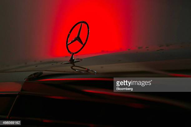 A hood ornament sits on a MercedesBenz SClass automobile as it sits parked outside the center of excellence showroom at Daimler AG's MercedesBenz...