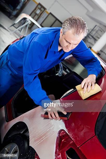Hood repair man polishing a red car
