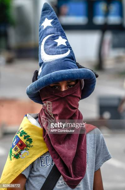 A hooded antigovernment activist wearing a hat looks on during clashes with the National Guard in Caracas on July 27 2017 on the second day of a...