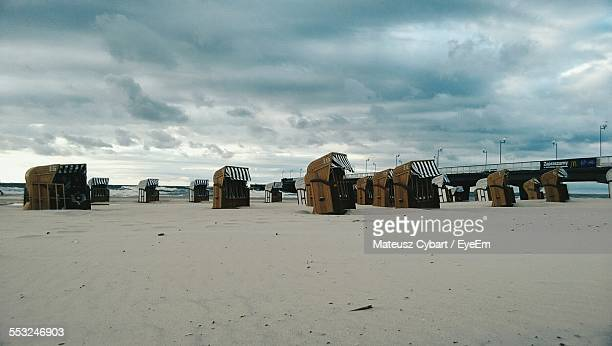 Hooded Beach Chairs At Shore Against Blue Cloudy Sky