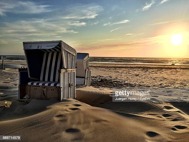 Hooded Beach Chairs On Sand During Sunset
