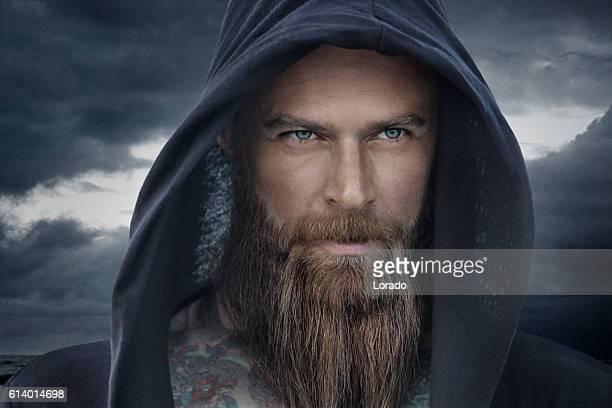 Hooded bearded tattooed male in fantasy cloudy seascape setting