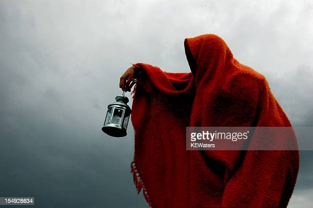 Hooded crone holds lantern in storm