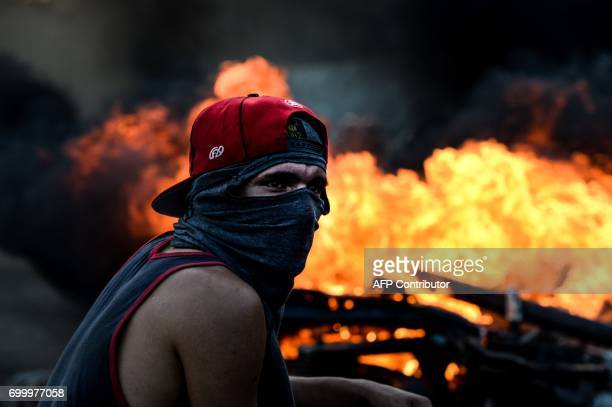 TOPSHOT A hooded demonstrator stands near a burning motorbike in clashes with the riot police during an antigovernment protest in Caracas on June 22...