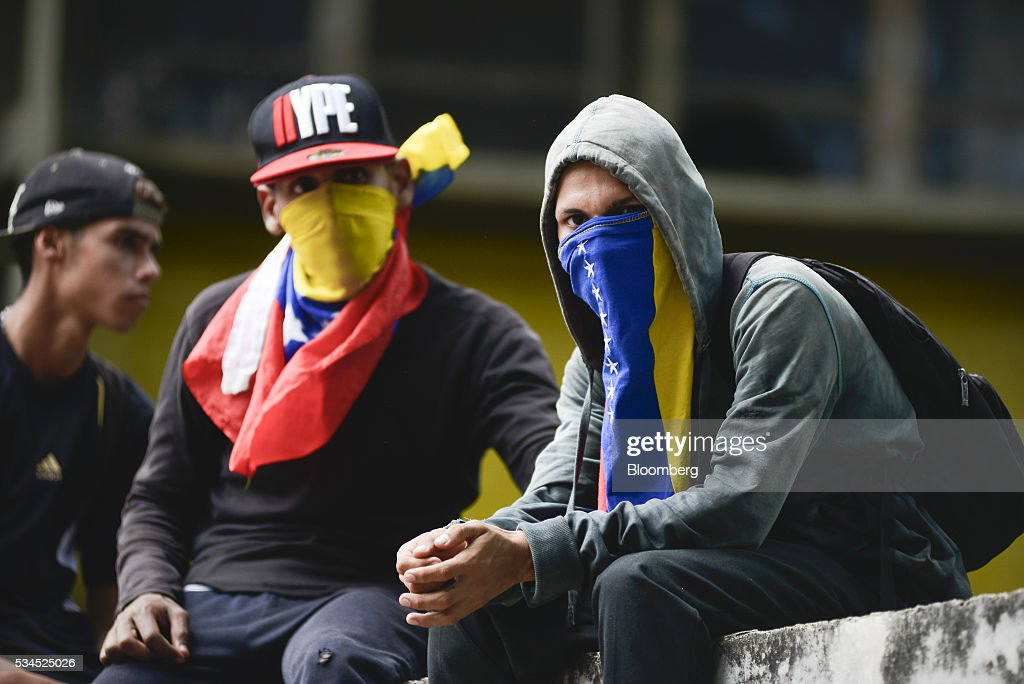 Hooded demonstrators sit near a pro-opposition march near the Central University of Venezuela in Caracas, Venezuela, on Thursday, May 26, 2016. The opposition is pushing for a recall referendum on President Nicolas Maduro and blame the 53-year-old leader for widespread shortages of food and basic necessities. Photographer: Carlos Becerra/Bloomberg via Getty Images